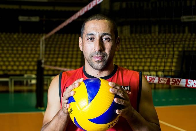 O Líbero Serginho Escadinha segura uma bola de vôlei em uma quadra de voleibol.