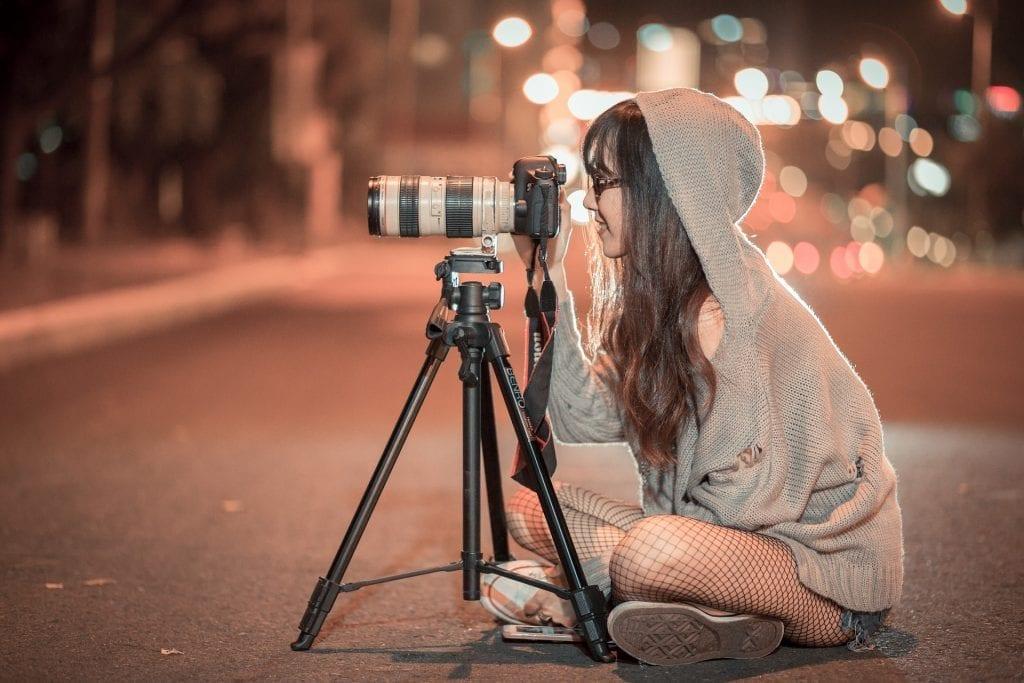 Moça ajusta lente de câmera para vídeo.