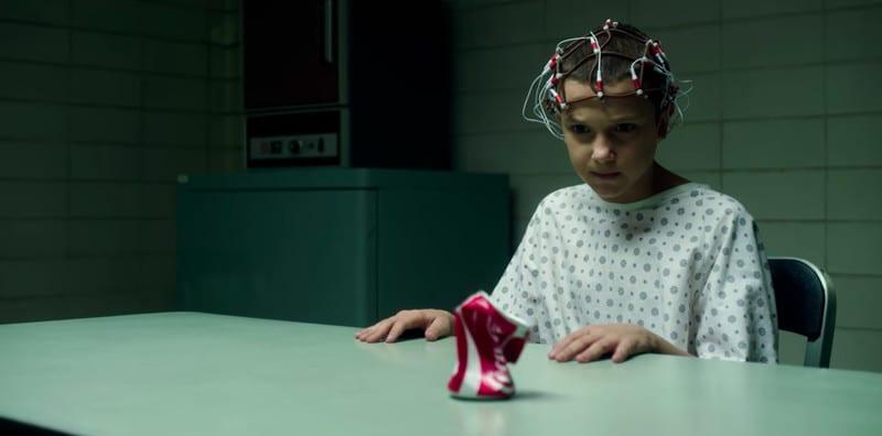 Eleven amassando uma latinha de Coca-Cola em um laboratório na primeira temporada de Stranger Things