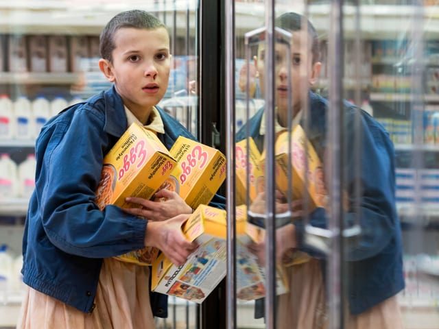 Eleven assaltando os waffles congelados Eggo de um supermercado na primeira temporada de Stranger Things
