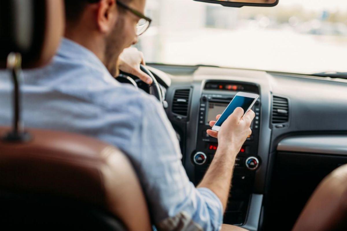 Dirigir veículo segurando telefone celular pode dar multa?