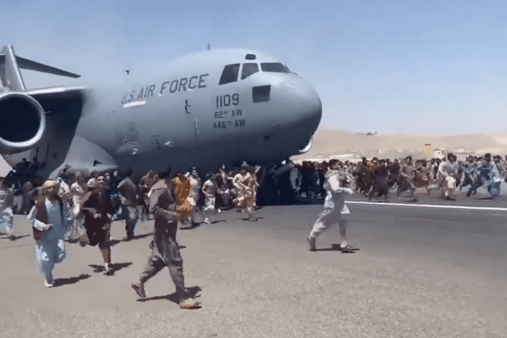 Pessoas tentam se segurar no avião pelo lado de fora para fugir do Afeganistão.