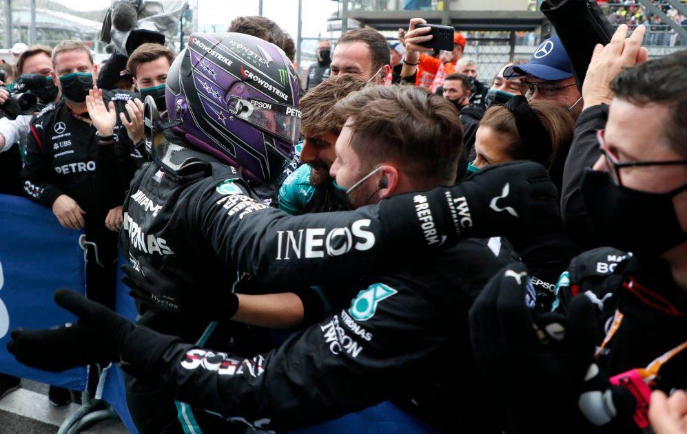 Lewis Hamilton comemora com a equipe após conquistar a centésima vitória da carreira.