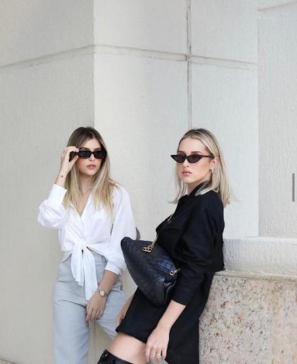 Maria Fernanda vestindo Camisa Vitoria Branca e Calça Marias Cinza, enquanto Maria Luiza veste Chemise Oversized preta